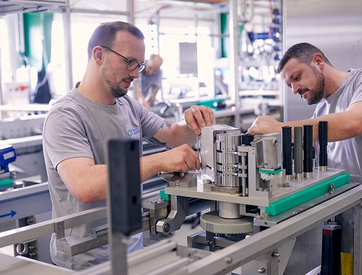 Two men reparing a machine
